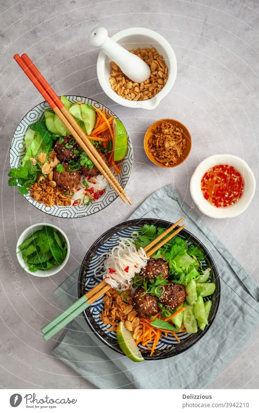 Top down view of two Vietnamese vermicelli bowls, Bun Cha, with fresh vegetarian ingredients, dipping sauce, peanuts and fried onions asia asian background