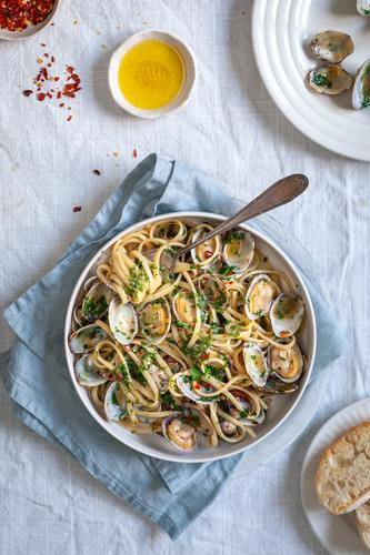 Top down view of pasta vongole, linguini with clams red pepper flakes and olive oil on white background with blue napkin food styling food photography