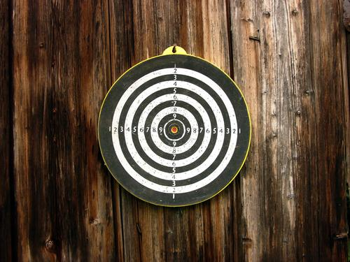 Round target for darts on the brown wood of an old barn on a farm in upper bavaria Target sheath Circle Sports free time entertainment Strike unerring figures