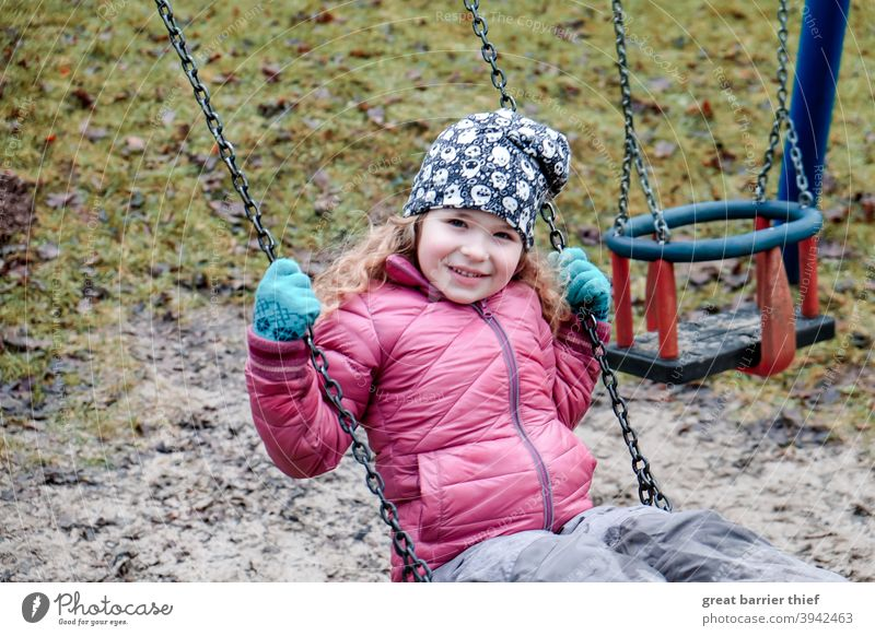 Girl on the swing Winter Playground To swing Swing Playing Child Infancy cheerful child Joy red jacket Laughter laughing child 3 - 8 years Nursery school child