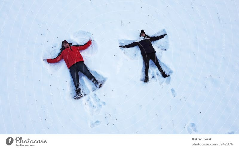 Drone shot of a woman and man making a snow angel while lying on the ground in winter Aerial photograph drone photo Woman Man Winter Snow Angel snow angels