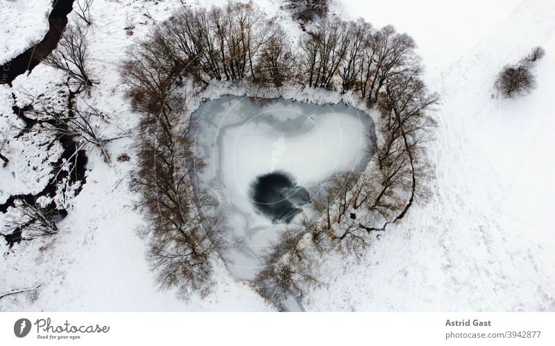 Aerial view from drone of frozen lake in heart shape or triangle shape in winter Aerial photograph drone photo Lake Body of water Frozen Ice Winter Snow