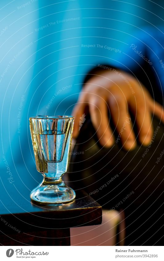 On a table is an old shot glass. The hand and arm of a person can be seen against a blue background. Schnaps glass Alcoholic drinks vodka alcoholism Alcoholics