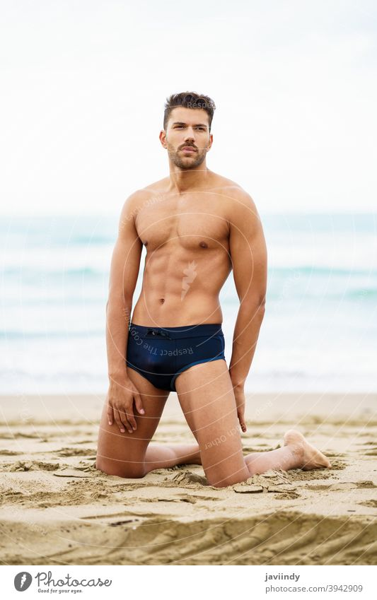 Handsome man on his knees on the sand of the beach sexy male muscular handsome healthy water people fit sea model abs vacation fitness chest strong attractive