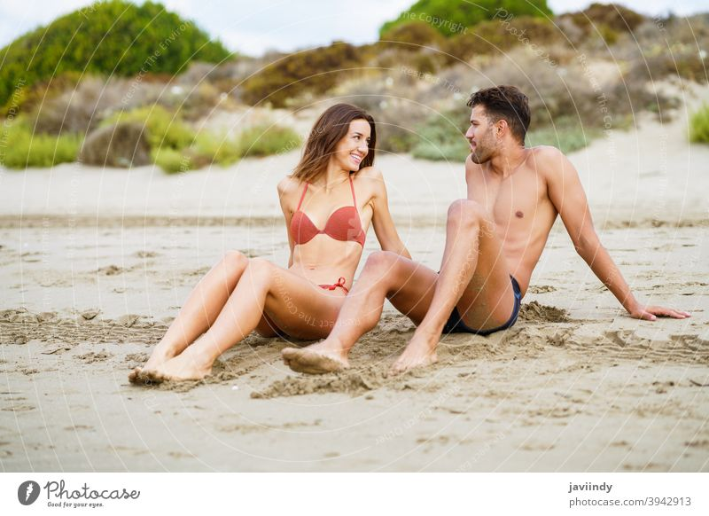 Young couple sitting together on the sand of the beach woman bikini summer body leisure lifestyle female girl coast outdoors enjoying people white swimwear fit