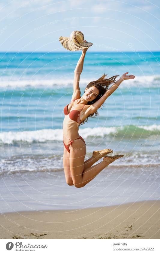 Young woman with beautiful body in swimwear jumping on a tropical beach. bikini swimsuit summer leisure lifestyle female girl coast hair one cute hairstyle joy