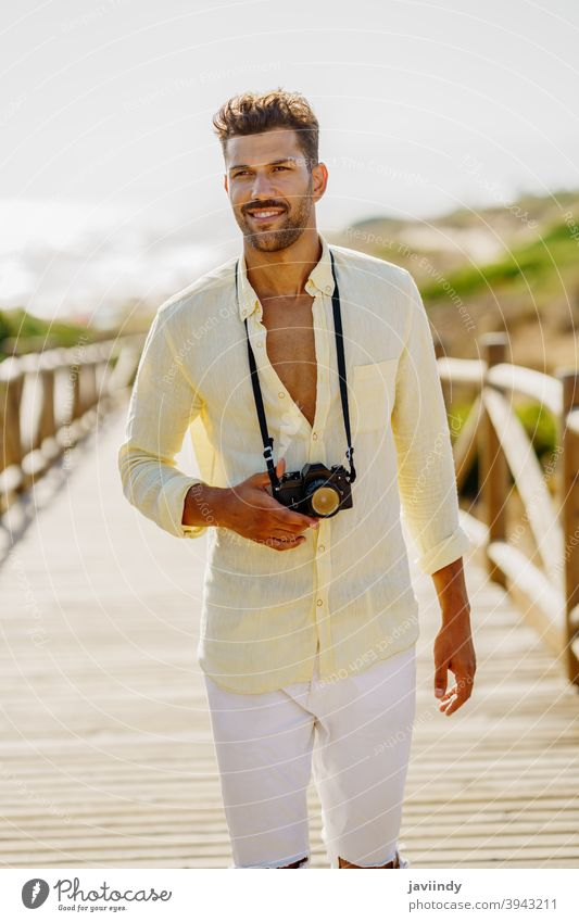 Smiling man photographing in a coastal area. photographer camera traveler tourist beach summer photography nature tourism vacation toothy smile holiday smiling