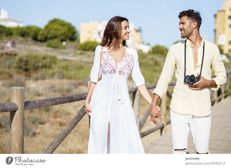 Loving couple walking along a wooden path towards the beach in a coastal area. vacation traveler tourist woman resort people holding hands love nature leisure