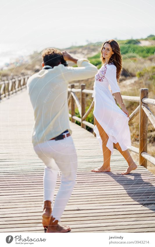 Man photographing his girlfriend on a lovers' trip. couple vacation photographer woman traveler tourist resort people nature leisure summer tourism spanish guy