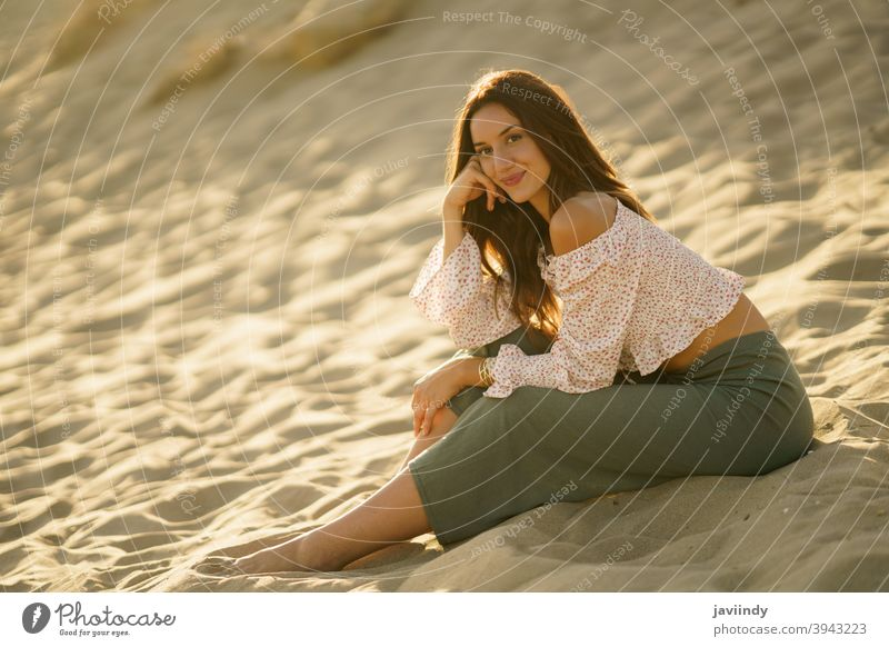 Attractive woman sitting on the sand of the beach adult person vacation caucasian female lady girl holiday relax outside young travel summer outdoors people