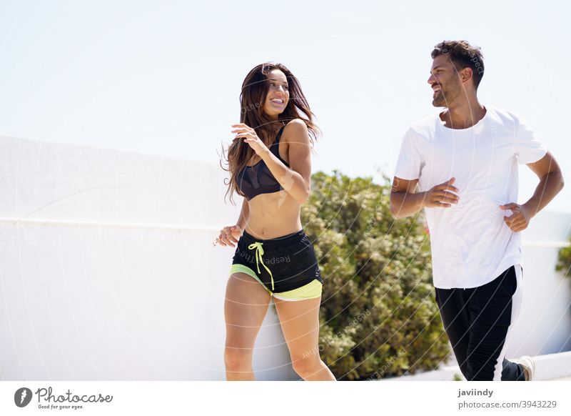 Young beautiful couple training together running outdoors fitness workout sport woman girl female activity young leisure jogger caucasian sportswear lifestyle