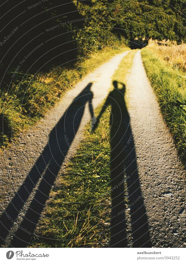 shadow couple holding hands walk romance romantic path walking stroll leisure park footpath woman boy girl casting long silhouette nature evening sun Love