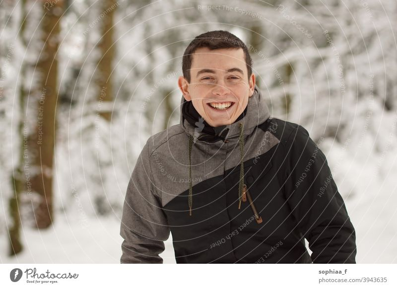 Winter - happy young man having fun in snow and laughing, smiling into the camera portrait winter teenager happiness joy boy guy cold skiing outdoor snowy male