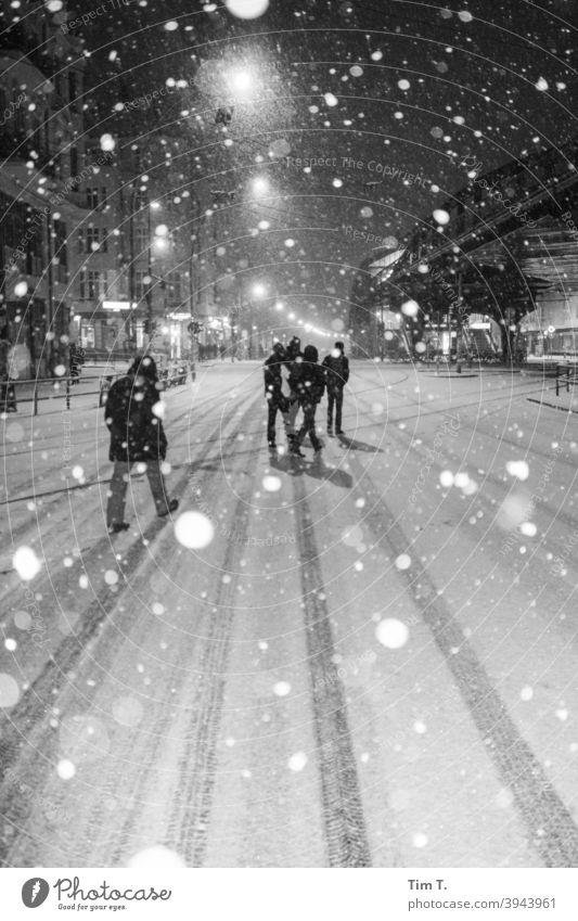 it is snowing in Schönhauser Allee Berlin b/w B/W Snow Winter Street Night night peoples Group Black & white photo B&W Exterior shot Town Dark iluminated