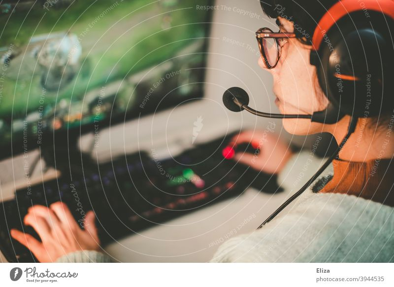 Young woman with headset playing games on PC. Gaming. Headset gaming Woman Playing gambling Technology Leisure and hobbies Computer games Calculator pc PC game