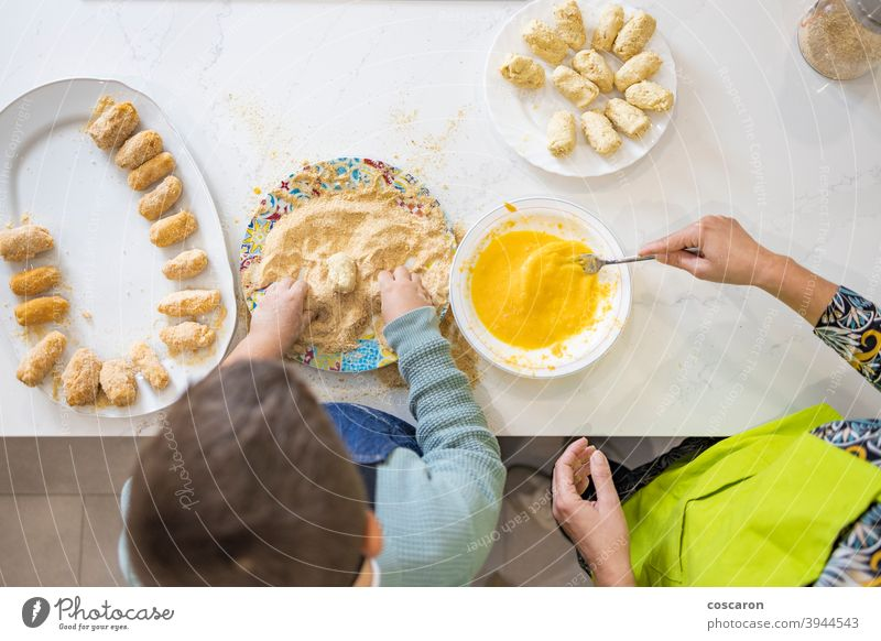 Mother and son making croquettes in the kitchen adult beautiful bowl bread crumbs caucasian child childhood cook cooking cute domestic dough egg eggs enjoyment