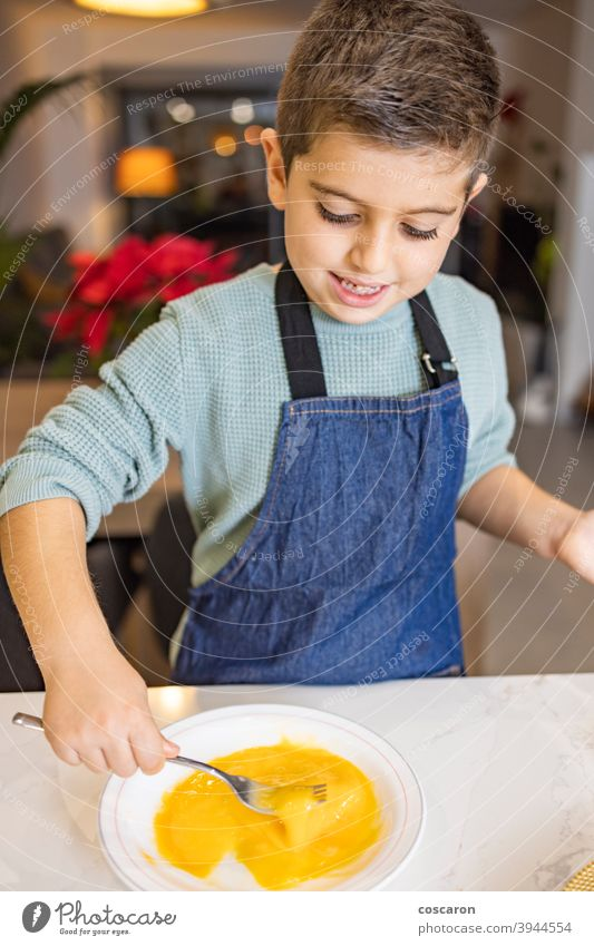 Little boy beating a egg in the kitchen activities baking biscuits bowl cake chef child childhood children cook cookies cooking croquettes cute dessert family