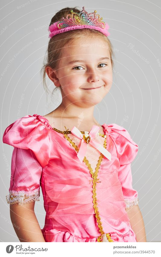 Little girl enjoying her role of princess. Adorable cute 5-6 years old girl wearing pink princess dress and crown fairy child festival lifestyle joyful smiling