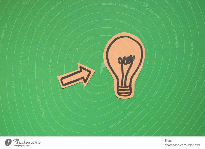 concept green electricity or have an idea. An arrow points to a light bulb on a green background. Idea Electric bulb Creativity incursion creatively innovation