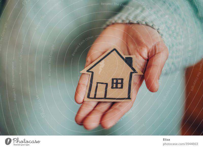 Hand holds a small painted house. Concept house construction and home ownership. House (Residential Structure) House building Home at home build a house
