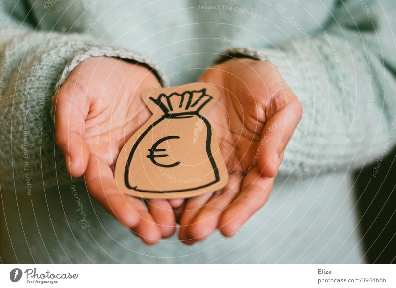 A person holds a painted money bag in his hands. Concept donor and donation. moneybags Donation Financial backer Give get Money finance investment Save spared