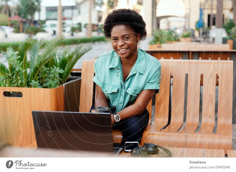 Portrait of a young African girl working at a laptop in a cafe during a coffee break. A break, relax, work online, freelancing woman beautiful bench using happy