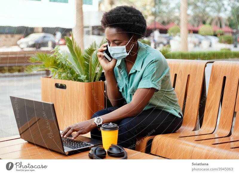 A young African girl in a medical face mask is talking on the phone and working with a laptop at a table in a cafe. Social distancing and work, work online, business online
