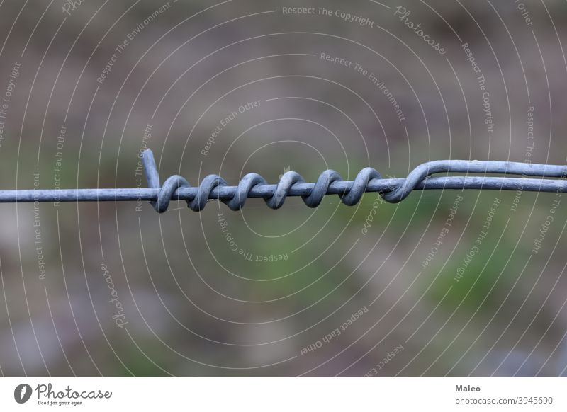 Twisting of metal wire on an electric fence steel prison protection sharp barbed barbwire barrier boundary detail energy spiral twist security crime criminal