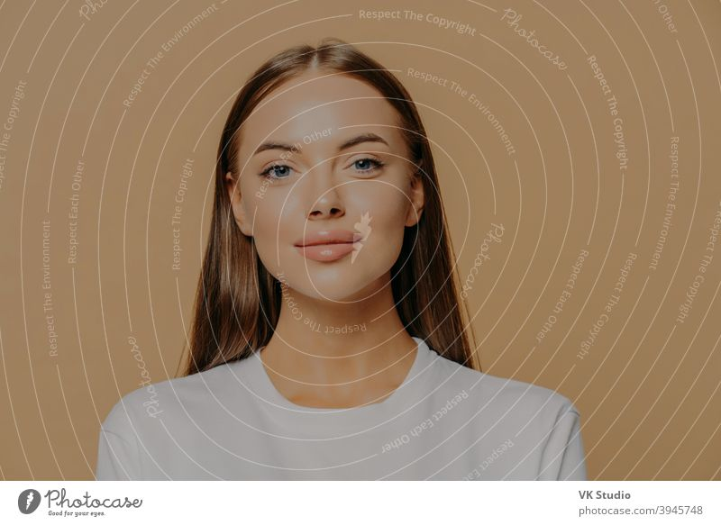 Portrait of pretty European woman with long hair looks confidently ar camera has healthy glowing skin makeup wears casual jumper isolated over brown studio wall. Beauty and wellness concept.