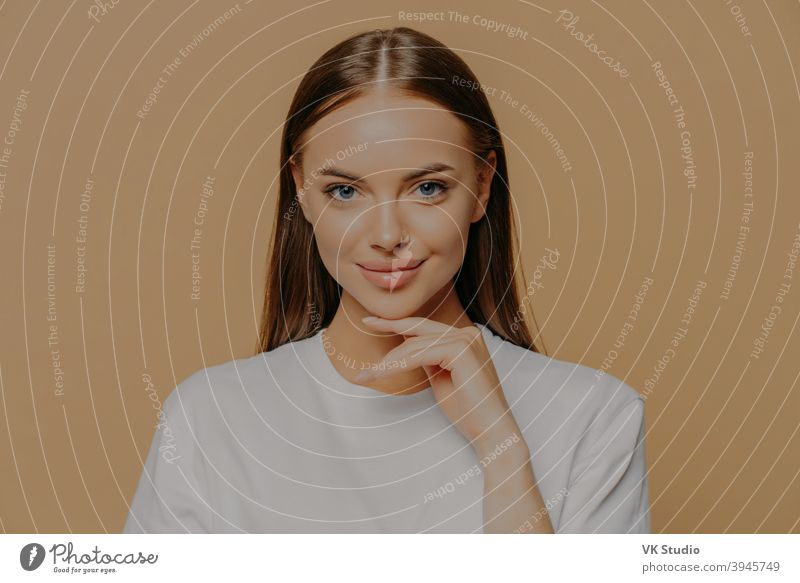 Lovely young European woman with makeup healthy skin touches gently jawline looks directly at camera has long straigh hair natural beauty dressed in casual sweater isolated over brown background
