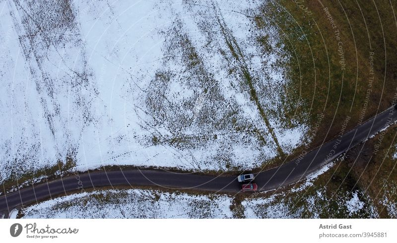 Drone photo of two cars passing each other in winter on a narrow road Aerial photograph drone photo Winter Street Driving Snow Sun Shadow Light Dark Warmth