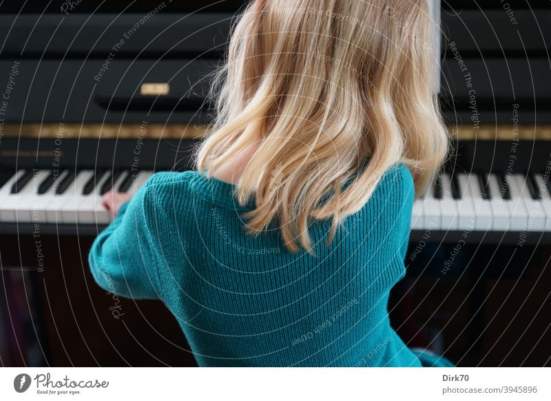 Little pianist - back view of blonde girl playing piano Girl Child Infancy Music Musician Piano Playing the piano piano player Keyboard Interior shot Make music