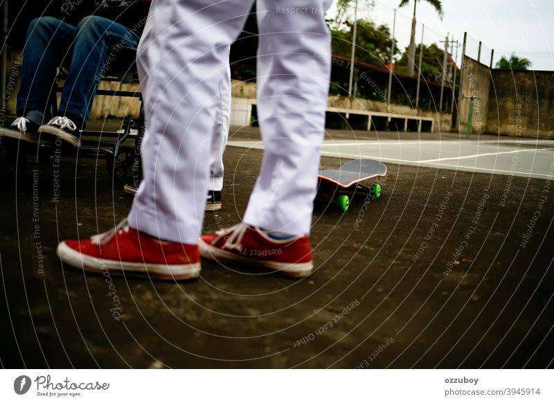 a boy in wheelchair with skateboarder friends playing in tennis court leisure life balance subculture background copy space real people equipment deck joy