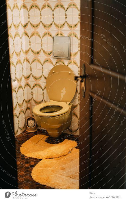 Retro toilet in bathroom Toilet john Flow nostalgically Nostalgia Bathroom Old Tile toilet brush Yellow Orange retro mood Old fashioned stale 1970s