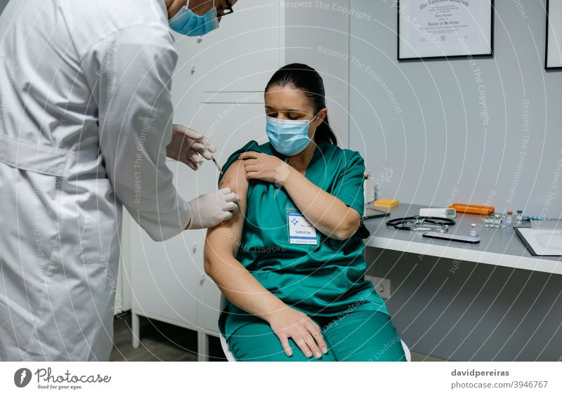 Female surgeon receiving coronavirus vaccine vaccination health workers covid-19 injection doctor clinic medical medicine professional doctors office specialist