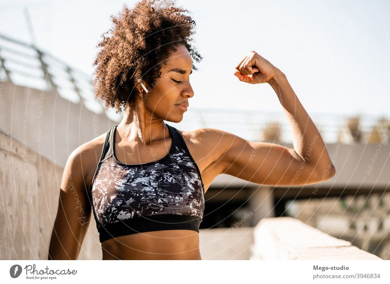 Afro athlete woman flexing and showing muscles. fitness sport exercise resting break outdoor relax enjoying relaxation leisure ear pods sporty relaxing