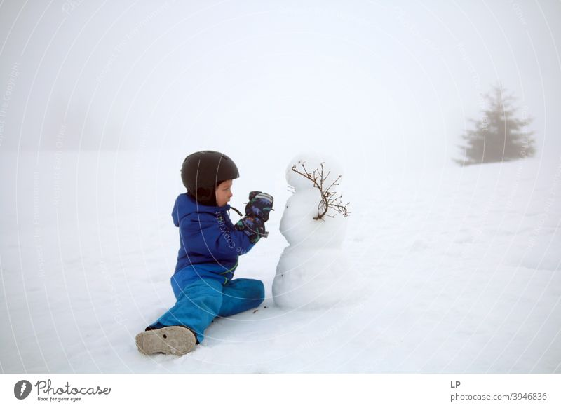 child making a snowman Snow Snowman Portrait photograph Exterior shot Delightful emotional seasonal Snowflake holiday Action kid Make Clothing Weather Nature