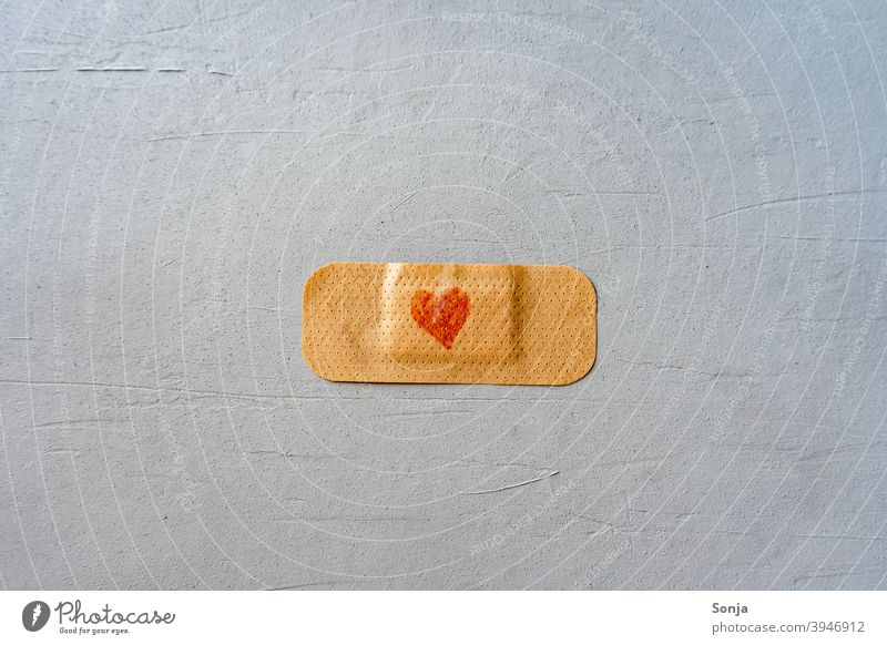 A plaster with heart on a gray background pavement Heart-shaped Red Immunization Healthy Virus Illness Hospital vaccine med Medical treatment coronavirus