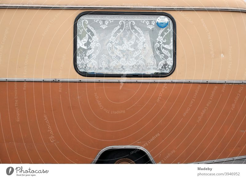 Skewered curtain with frills in the window of an old caravan of the fifties and sixties in two-tone varnish in beige and brown at the Golden Oldies in Wettenberg Krofdorf-Gleiberg near Gießen in Hesse