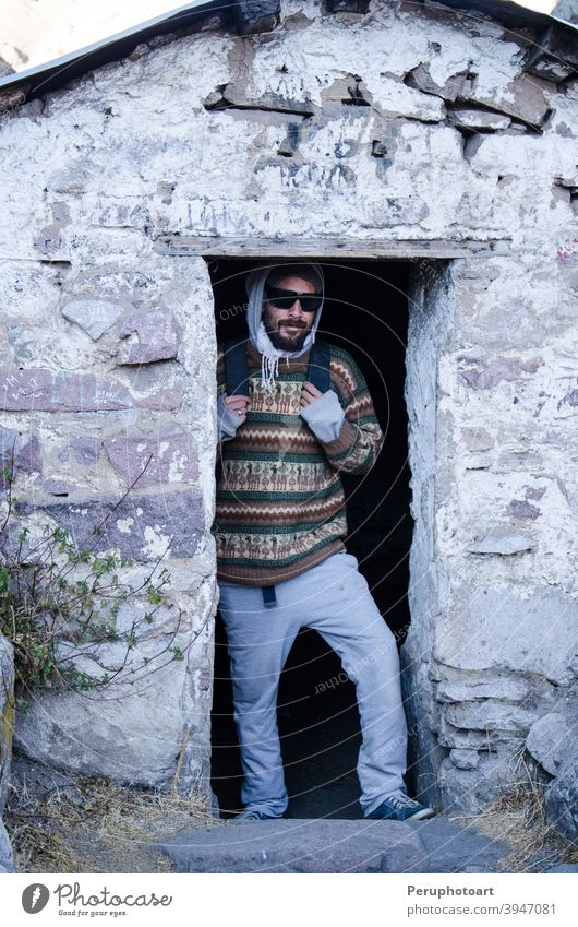 Traveling man with glasses poses in front of Daniel Russo's house in Marcahuasi Mountain travel Adventure Climbing Success Man height Extreme Nature Rock Sports