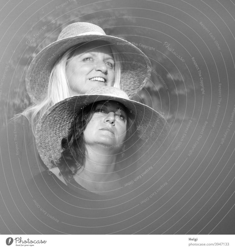 Faces of two ladies in straw hats, one looking up seriously, the other looking forward with a smile Human being Lady Woman Straw hat Long-haired Blonde Brunette