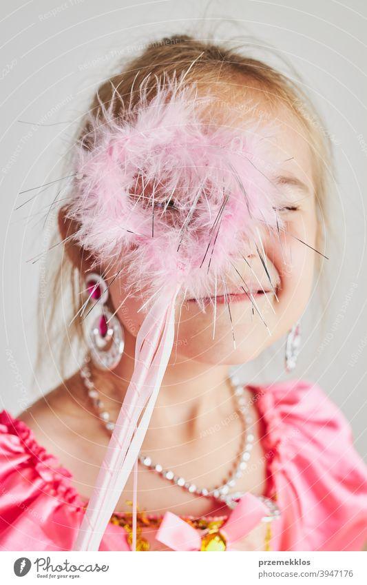 Little girl enjoying her role of princess. Adorable cute 5-6 years old girl wearing pink princess dress holding magic wand fairy child festival lifestyle joyful