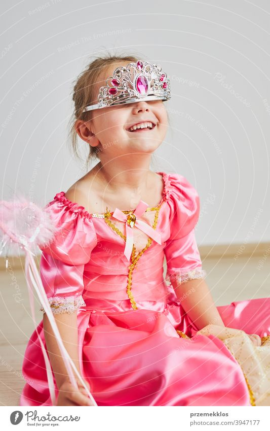 Little girl enjoying her role of princess. Adorable cute 5-6 years old girl wearing pink princess dress and tiara fairy child festival lifestyle joyful smiling