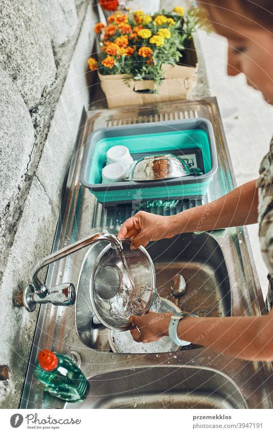 Woman washing up the dishes pots and plates in the outdoor kitchen during vacations on camping campsite cleaning cleanup detergent dirty dish wash dish washing