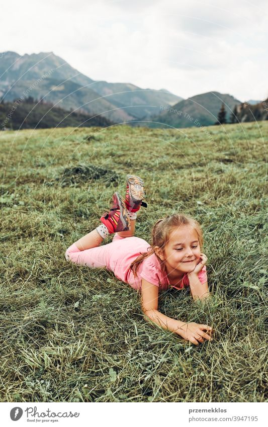 Little girl laying playing on grass enjoying summer day during vacation trip happy excitement enjoyment leisure emotion positive lying lifestyle activity