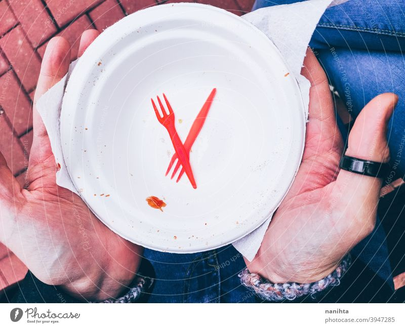 Disposable plate and cutlery disposable dish empty single use trash knife plastic microplastic fork hold holding picnic hands man male young no sustainable