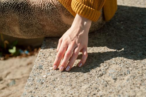 Closeup of female hand touching stone stairs outdoors lifestyle girl nails accessories closeup detail stones arm finger woman spring season summer details