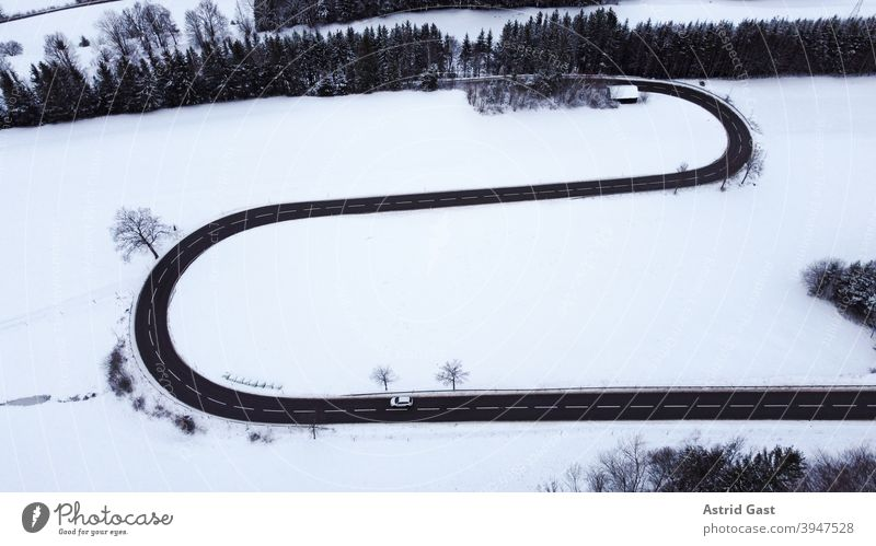 Aerial shot with a drone of a road curve with a moving car in winter Aerial photograph drone photo Winter Street Driving Snow Curve hairpin bend road bend curvy