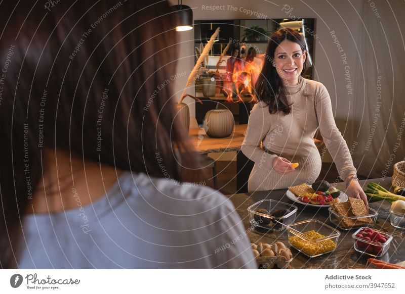 Pregnant Woman Cooking preparing healthy dinner meal pregnant woman pregnancy friends friendship at home kitchen salad eating vegetables counter table together