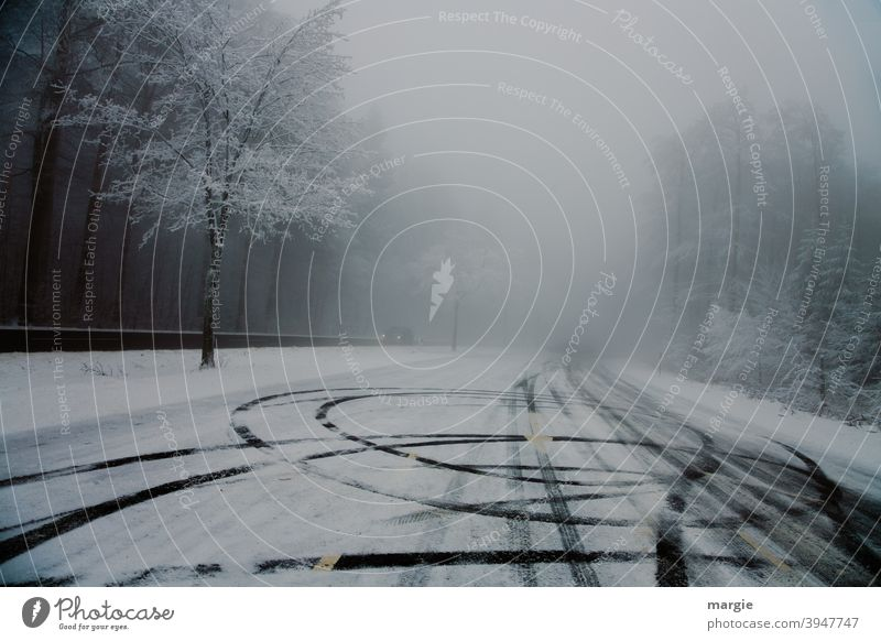Tire tracks on a slippery road with snow and ice Street trees Forest off Winter Skid marks car Headlamp Tracks Black ice smooth as folded asfalt street Deserted